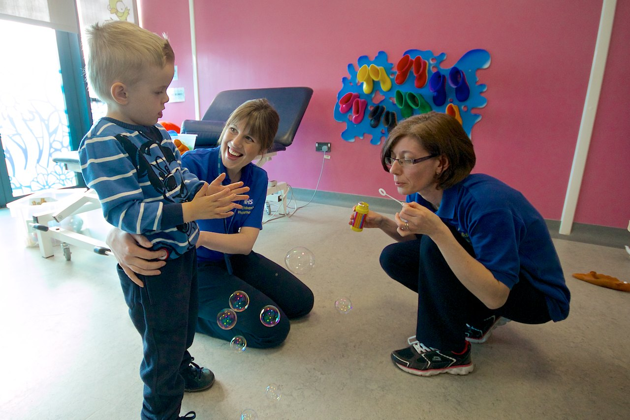 Boy catching bubbles blown by two physiotherapists