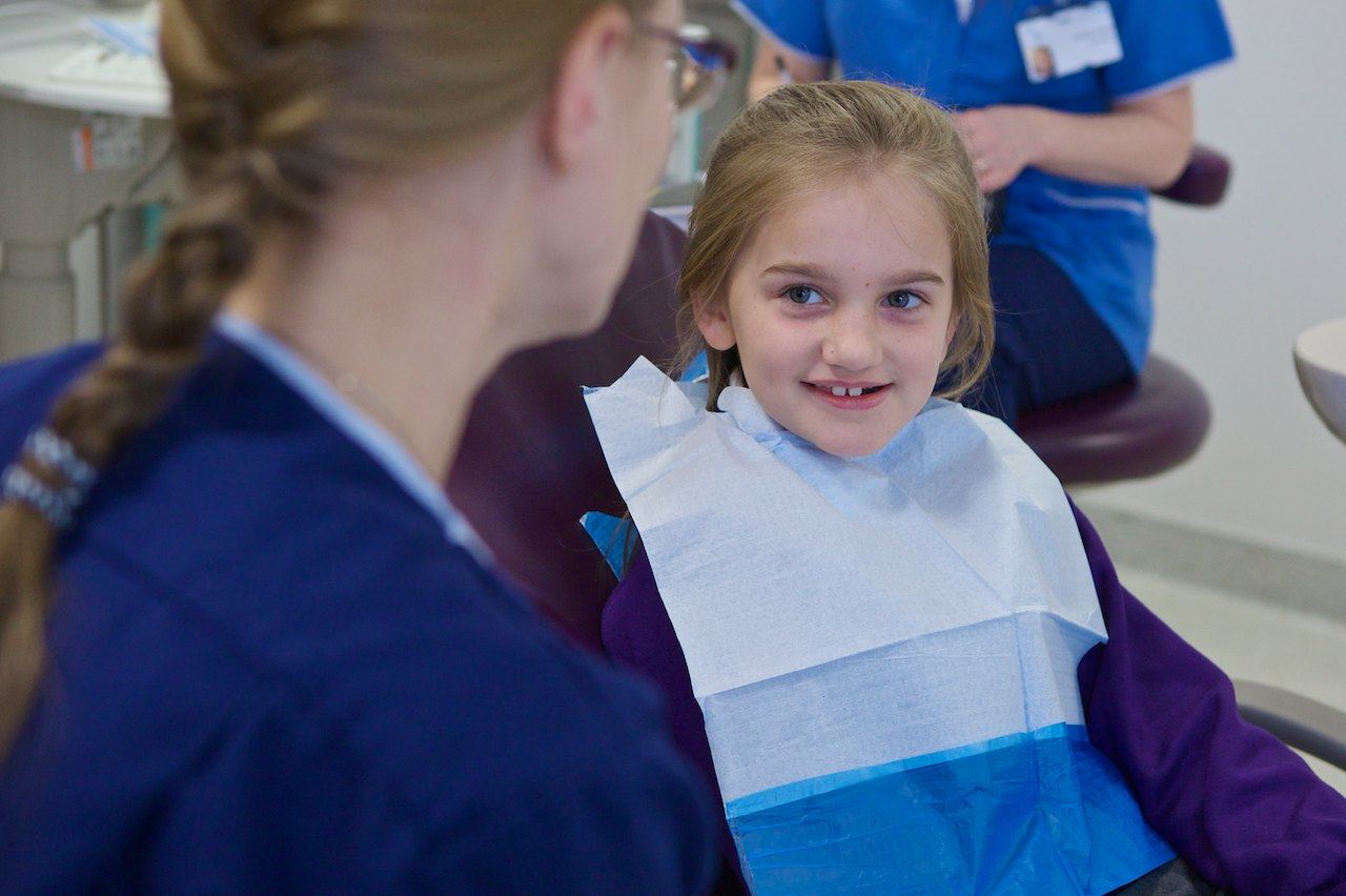 Girl in chair looking at dentist