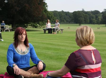 Women sitting with eyes shut and crossed legs in a park