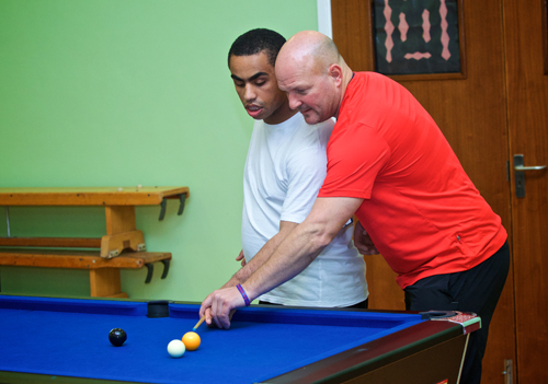 A staff member helps a service user to play pool