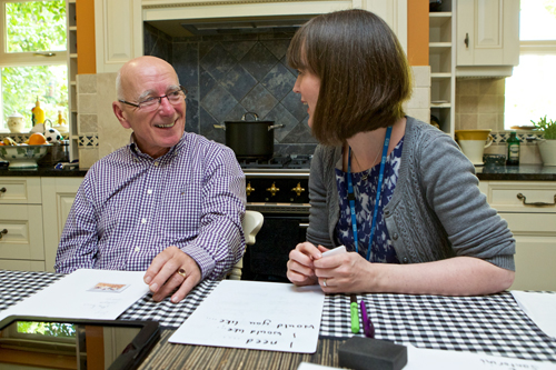 A speech and language therapist working with a man at home