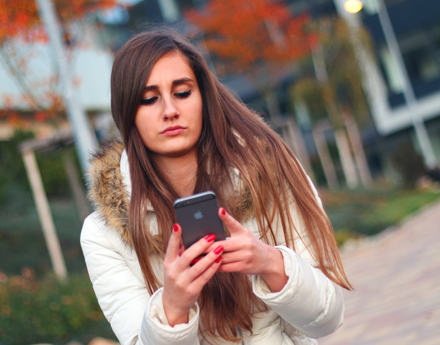 A teenager looking at her mobile phone