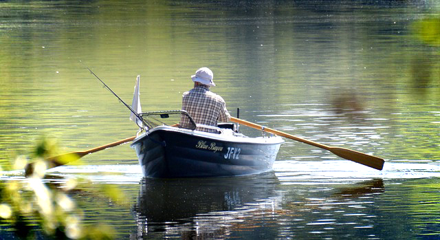 A man in a rowing boat on a lake