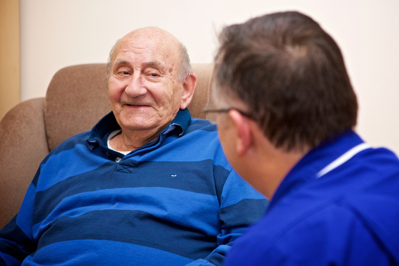 An elderly man smiling at a nurse