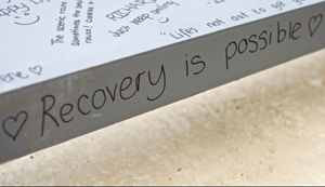 A steel girder with messages written on it, including the words 'recovery is possible'