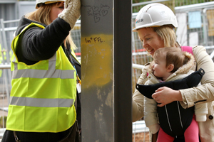 A mother and baby take part in a steel signing event