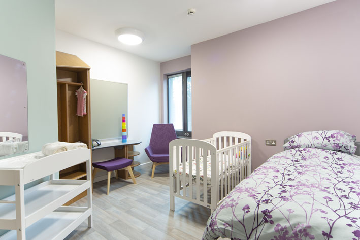 A homely room with a crib in the Mother and Baby Unit