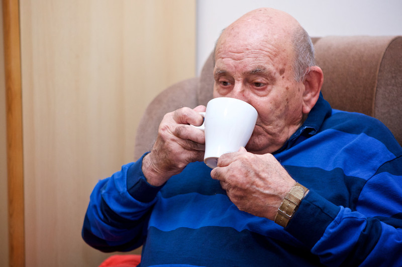 An older man drinking a mug of tea